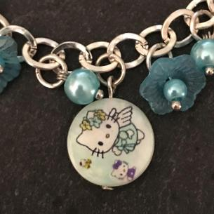 Close up view of kitty shell coin on the bracelet.