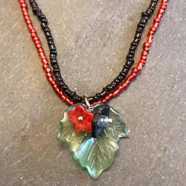 Necklace made from red and black seed beads with a flower and leaf pendant.